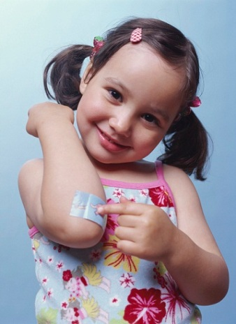 Girl with bandaid on elbow --- Image by © Royalty-Free/Corbis